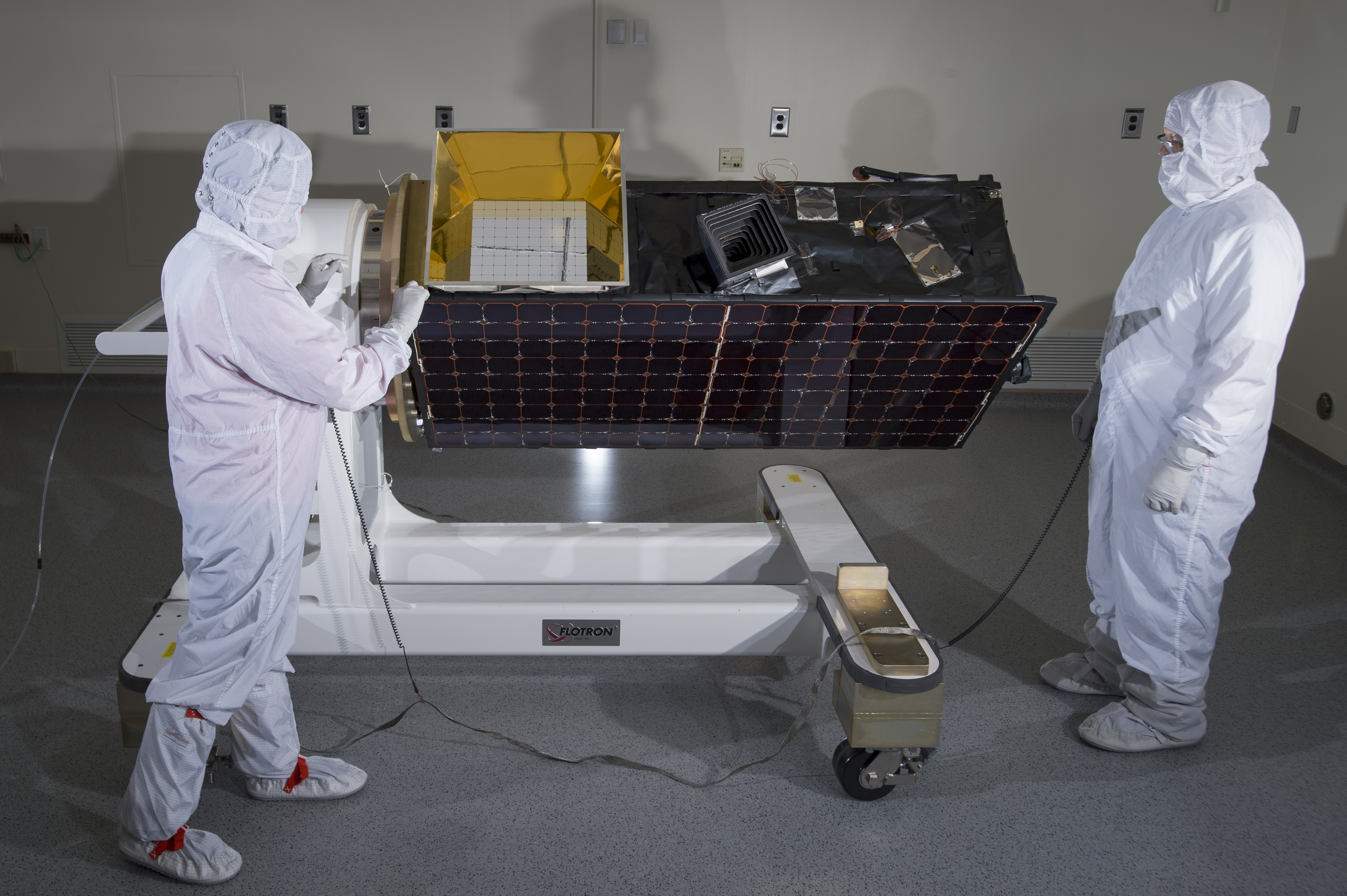 An engineer inspects SensorSat prior to thermal-vacuum testing. Photo: Glen Cooper
