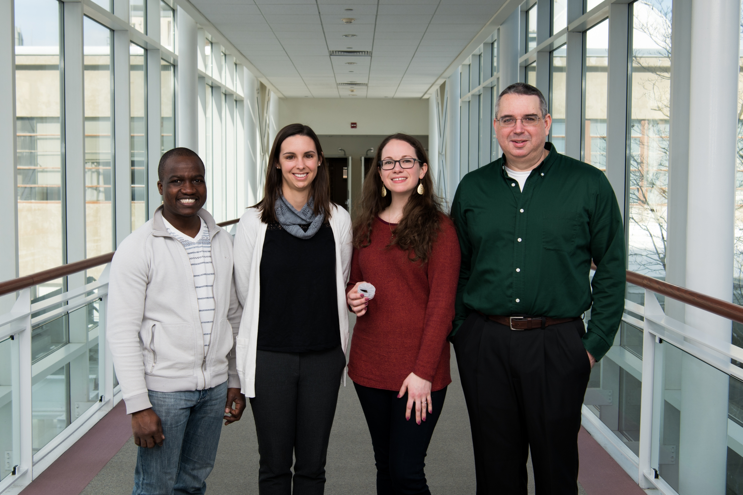 The team of four researchers pose for a group photo in a hallway