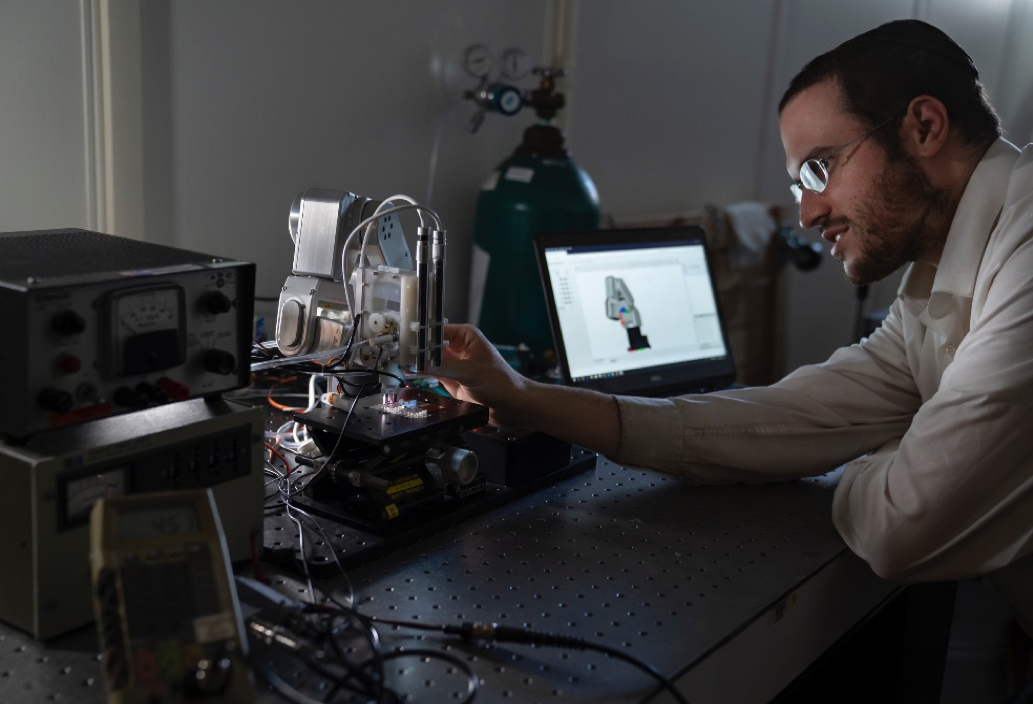 A man adjusts the microplasma sputterer setup, which looks similar to a small 3D printing arm and nozzle, depositing material onto a metal plate.