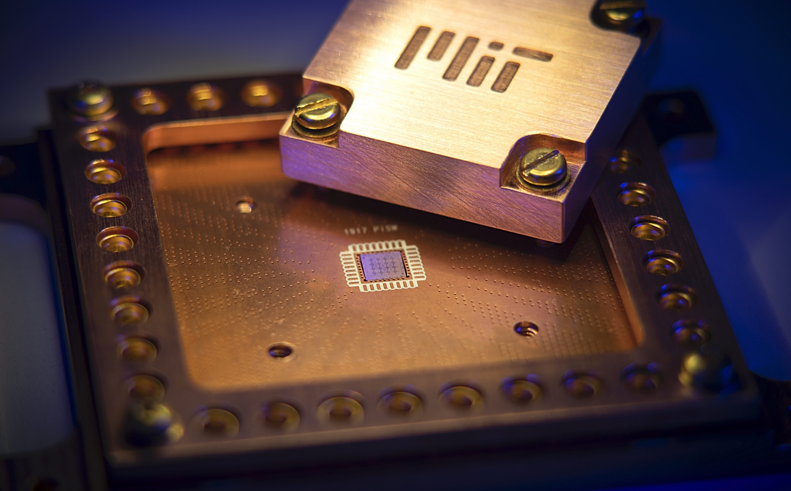 A photo of a quantum chip with MIT etched into metal.