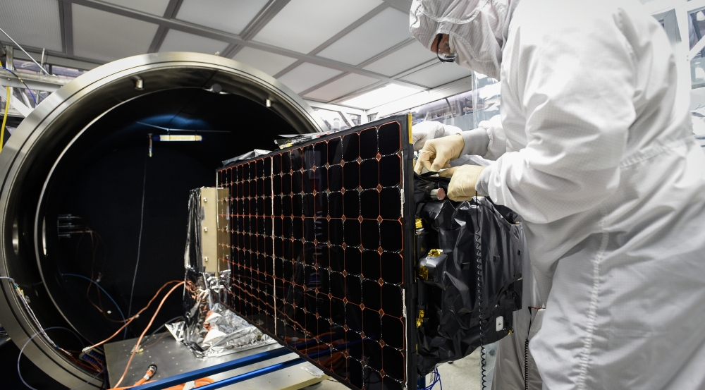 An engineer is installing SensorSat in the thermal-vacuum chamber used for testing the satellite's tolerance of conditions in space. Photo: Glen Cooper