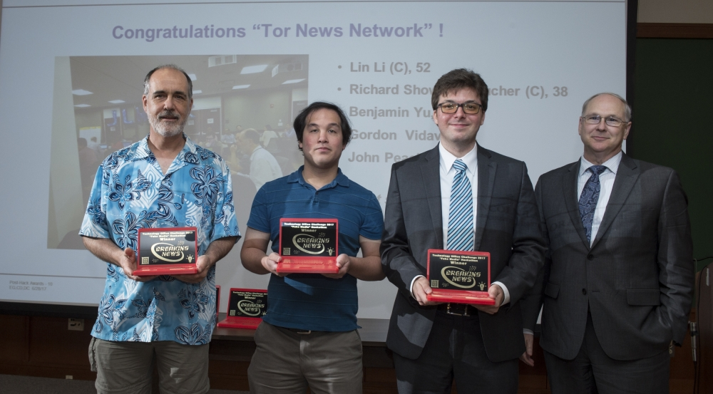 Members of the winning team, Tor News Network, accept trophies presented by Bob Bond, Chief Technology Officer.