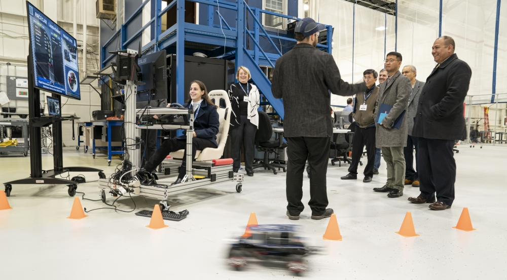 Attendees of the RAAINS workshop learn about the Laboratory's RACECAR platform during a tour of the Autonomous Systems Development Facility.