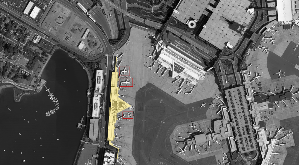 A goal of the program is to develop a system that can identify spatial relationships between objects in a scene, such as counting how many planes are parked at the terminal on the left.