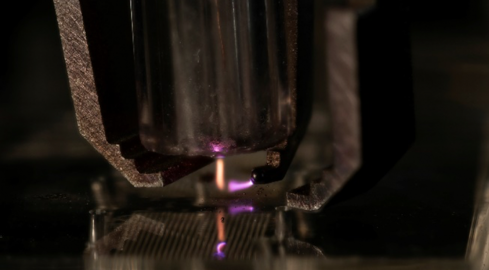 A zoomed-in view of a metal nozzle shooting a stream of orange onto a metal surface, and a nozzle shooting a stream of purple at the orange stream of material.