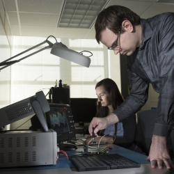 A photo of two staff members with electronic equipment in front of them in a lab