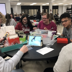 A group of five high school students sit at a table, smiling, working together to assemble a robot out of what look to be lego-like parts.