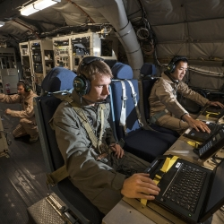 Lincoln Laboratory personnel Joseph Zurkus, left, and Jacob Huang, right, operate a protected tactical waveform modem and collect data while Ted O'Connell, back, monitors terminal equipment during flight testing.