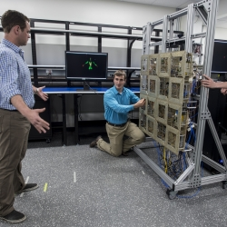Researchers test the prototype standoff microwave imaging system. The antennas emit radio signals that reflect off the person standing in front of the array; the system processes the reflections to create the image on the monitors in the background.