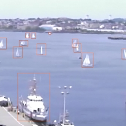a photo of boston harbor with several boats on the water; each boat has an orange box drawn around it as a 'detection'