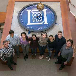 5 students and 3 mentors pose in front the Laboratory's pendulum.
