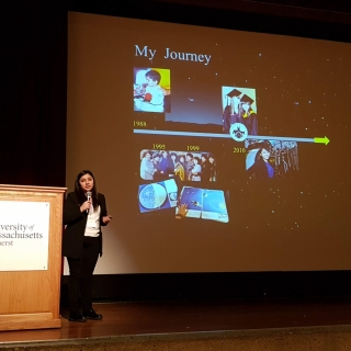 "Yari Golden-Castano stands on stage in front of a slide titled ""My Journey"" as she gives a plenary talk."