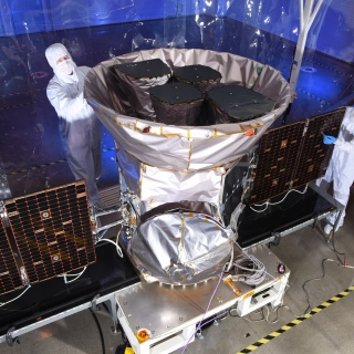 A photo of two scientists inspecting the tess satellite in a cleanroom environment.