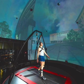 A woman, attached to a harness, stands on a treadmill, and is surrounded by a spherical screen displaying a city scene.