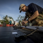 Erik Limpaecher connects cables to solar panels on a roof