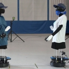 Two robots (dressed as human mannequins) face eachother.