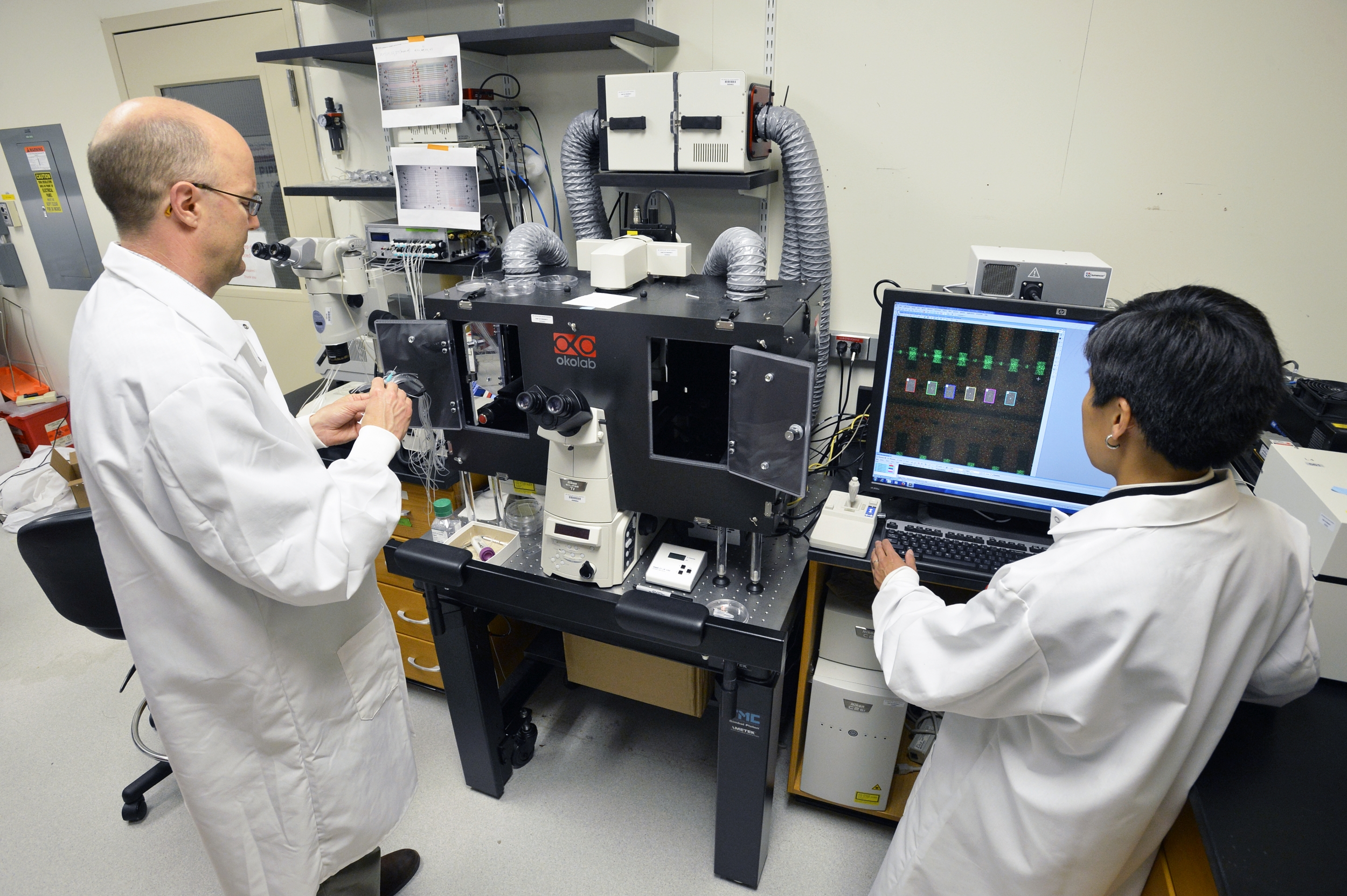 Two researchers in white lab coats stand in front of a large microscope and monitor.