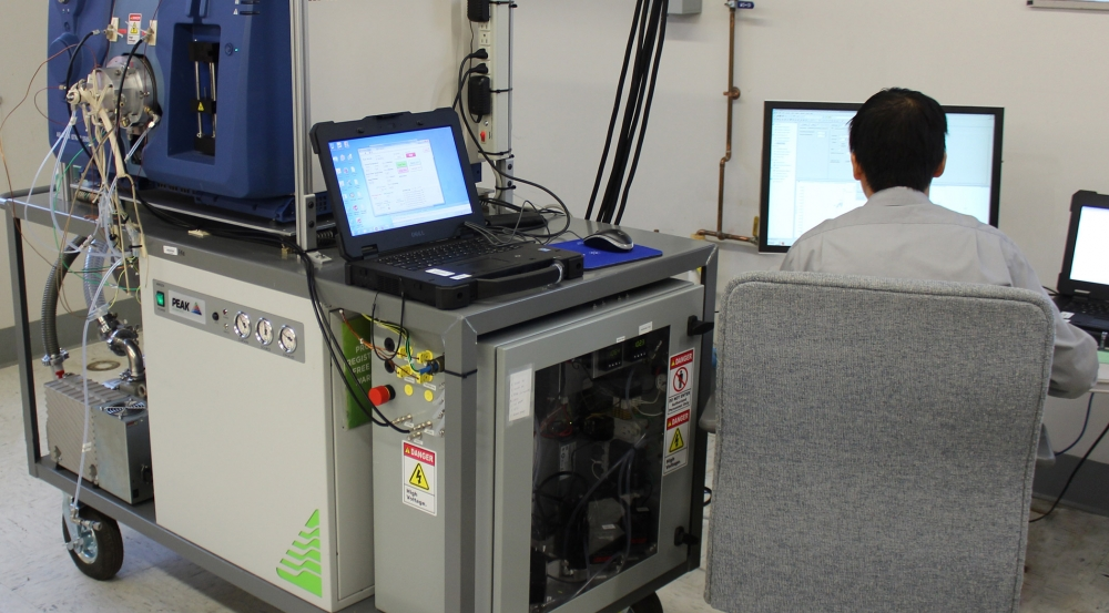 A researcher sits a monitor next to a mass spectrometer as it conducts measurements.