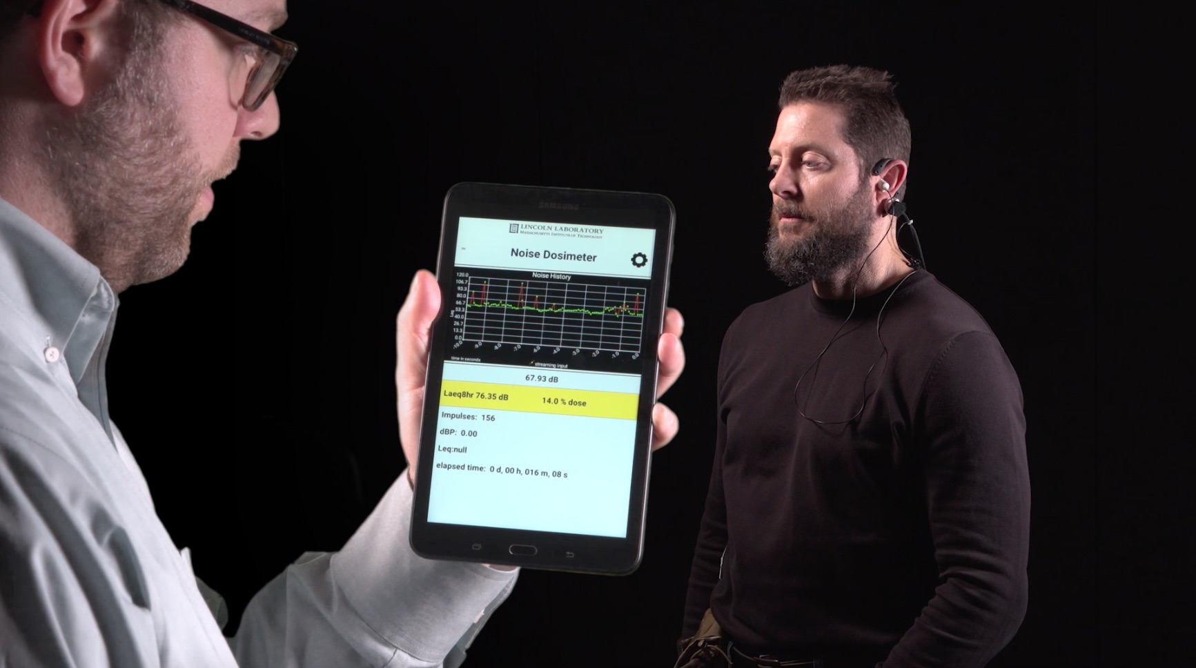 A researcher holds a tablet showing the MNOISE app while a user wears the MNOSIE earpiece.