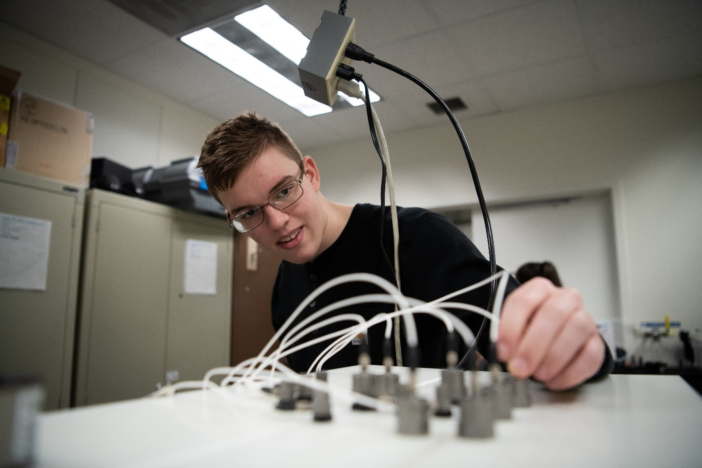 Andrew O'Brien adjusts transducers in a laboratory