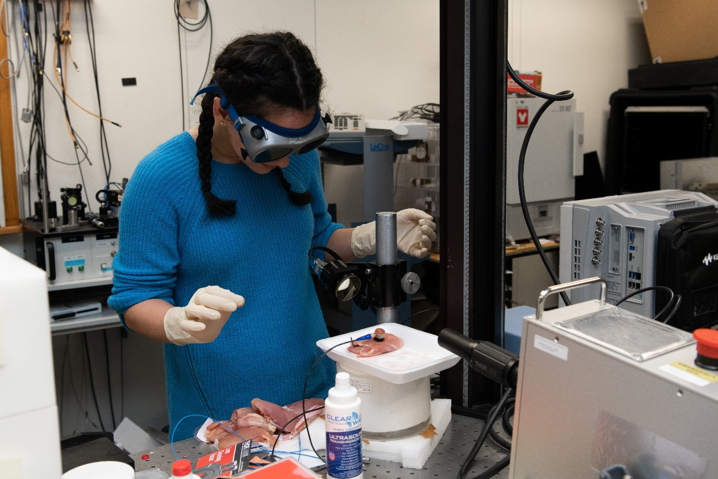 A student in a laboratory places a piece of chicken on a vibrometer.