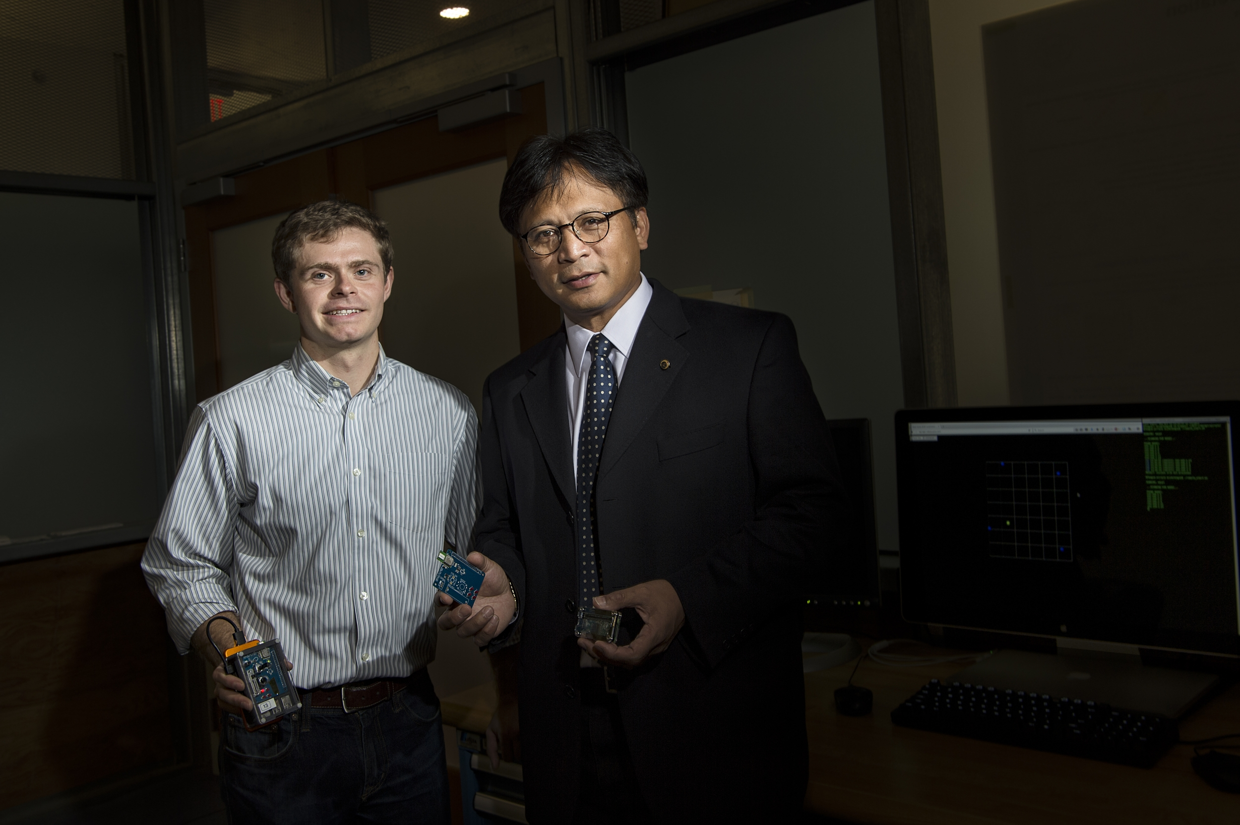 Two researchers pose for a photo in lab holding a small electronic device