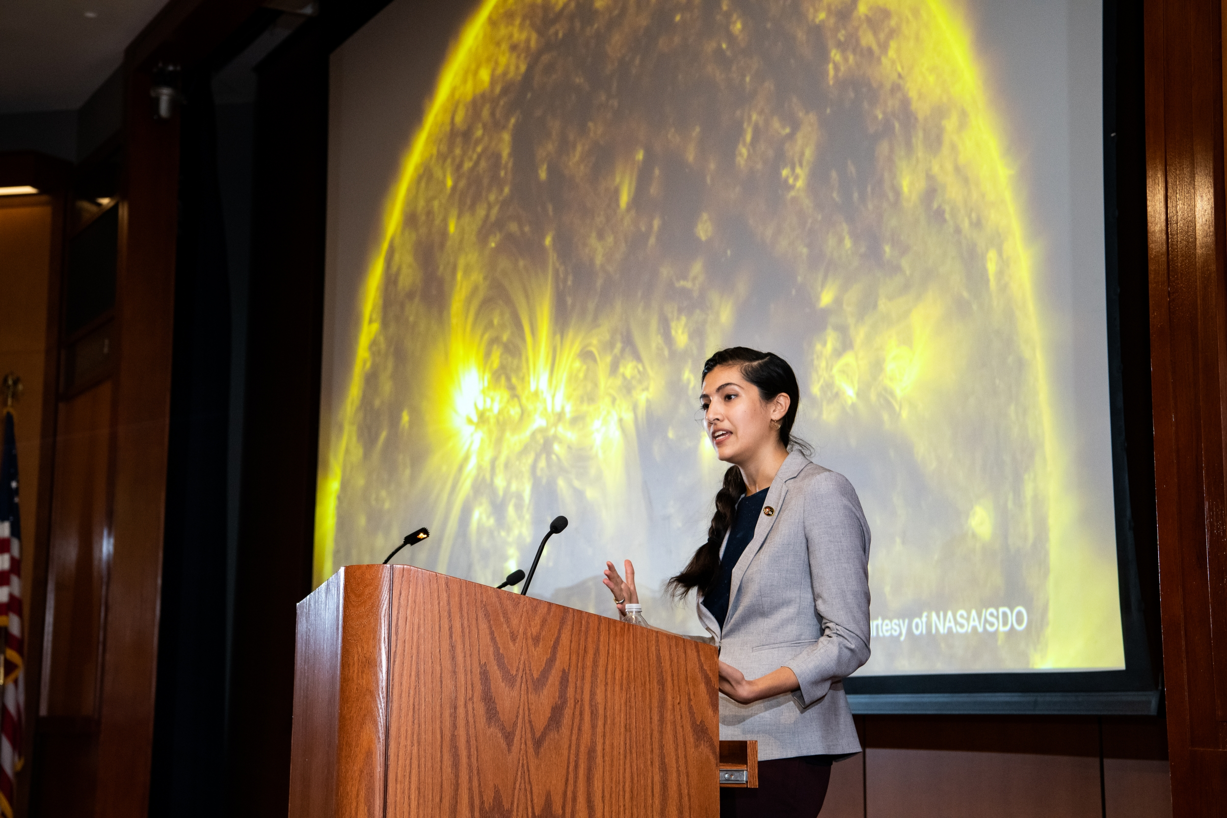 Natalia Guerrero stands at the lecturn and gives her keynote speech in front of a large image of a sun