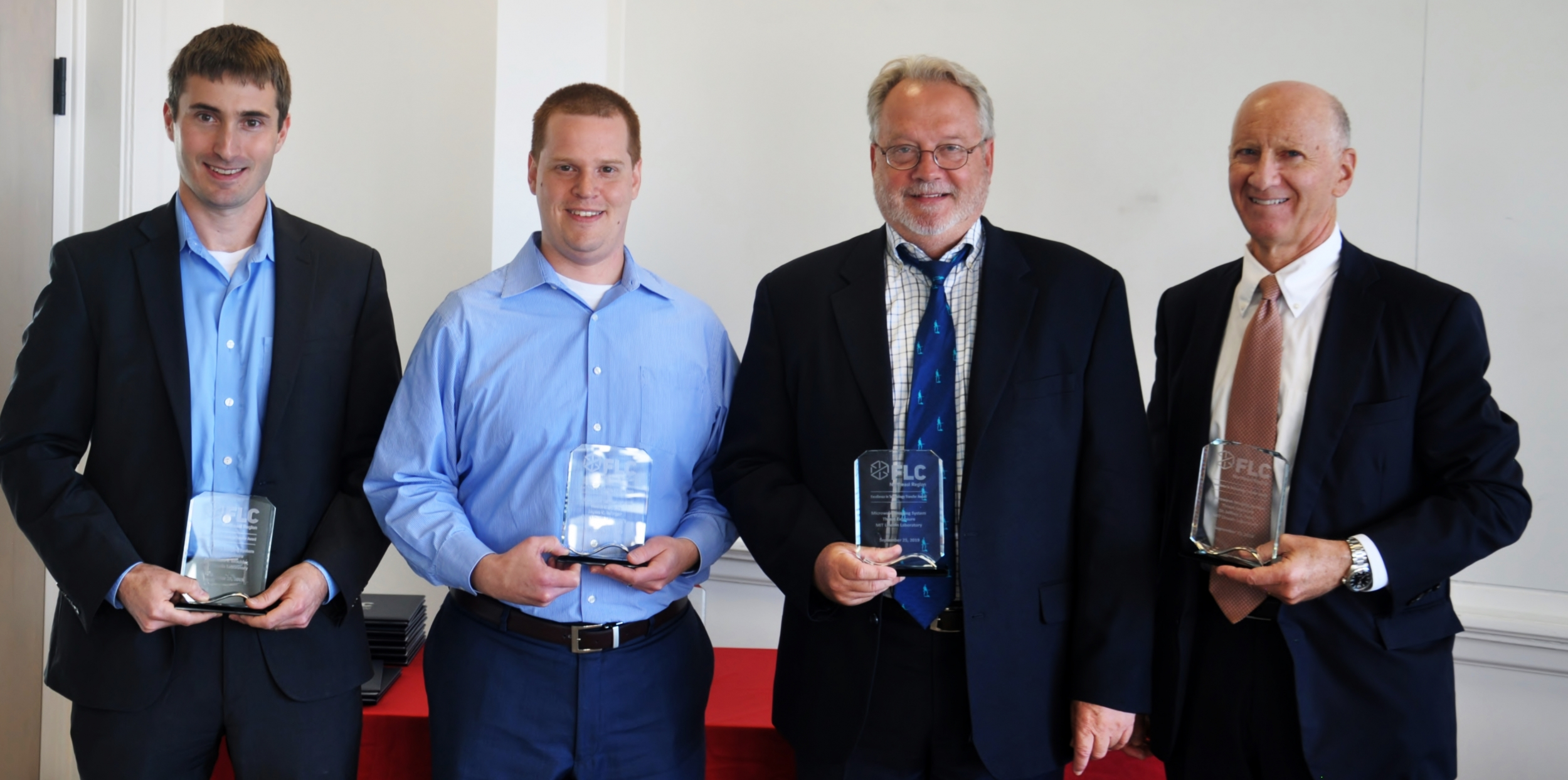 Four lincoln laboratory staff members stand each holding a glass award.