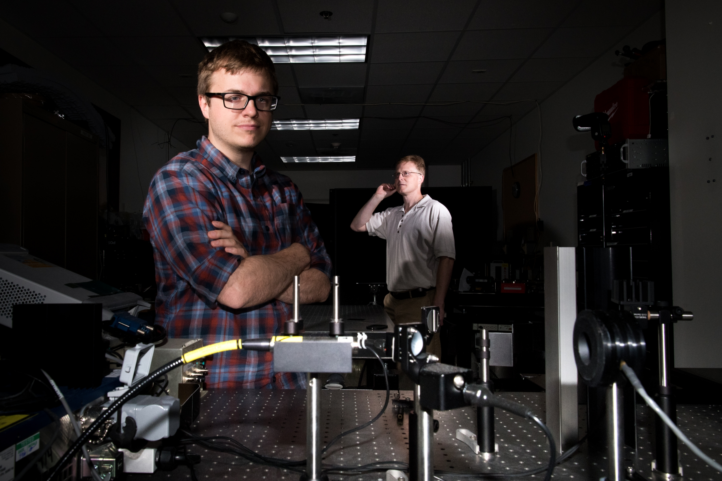 Two men standing in a laboratory with a laser transmitter setup