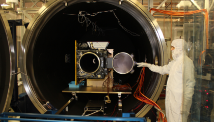 Engineers load a satellite into an ETL space simulation chamber for testing.