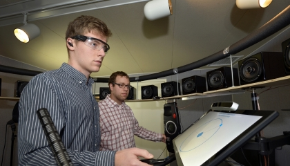 Two staff members stand in a room surrounded by speakers and use a system to select which speaker a sound is coming from.
