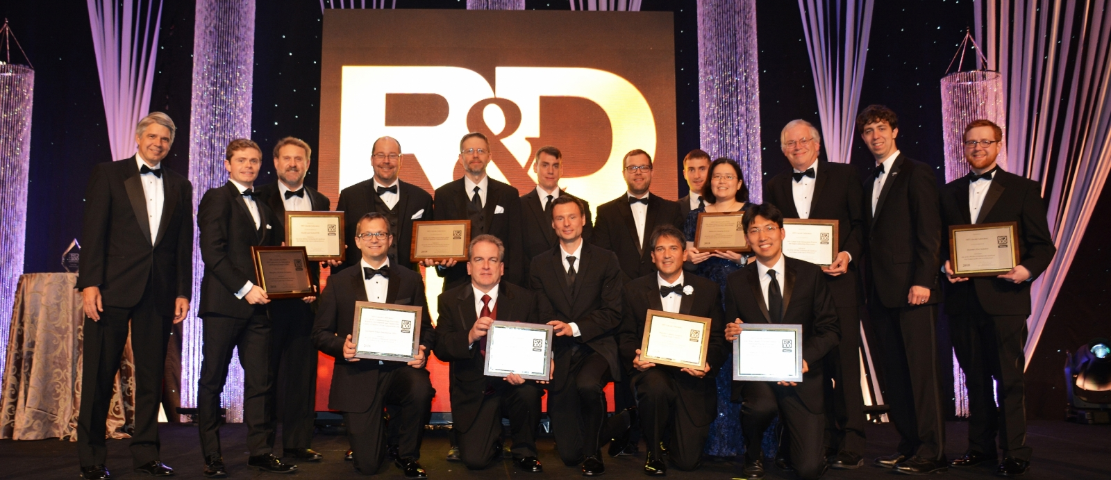 The principal researchers of MIT Lincoln Laboratory's 12 finalists for 2018 R&D 100 Awards are pictured here with Lincoln Laboratory Director Eric Evans (far left). The principal researchers of the 10 winning technologies hold up their award plaques.