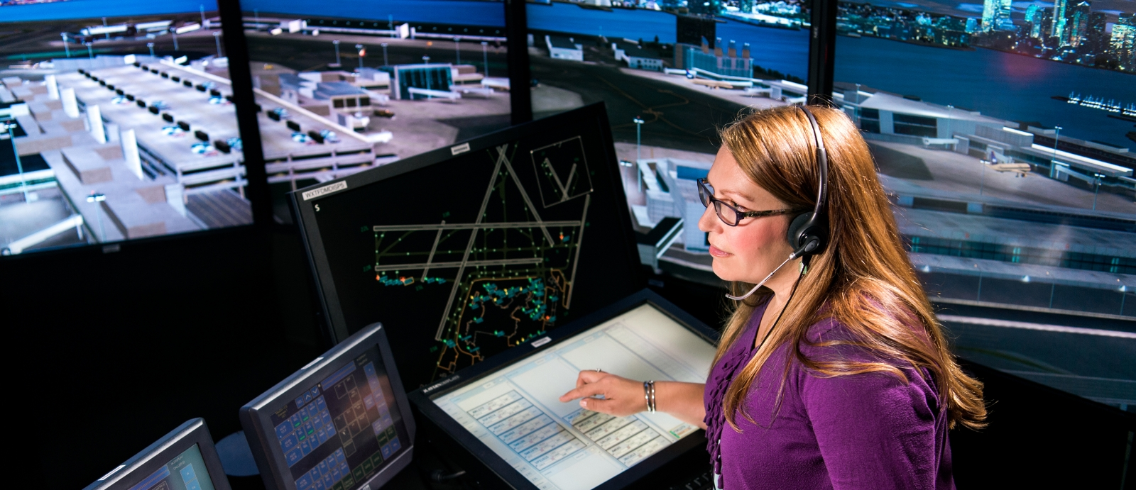 In the control tower simulation facility, an Air Traffic Control Systems staff member uses integrated electronic flight data and surveillance systems to direct an aircraft to taxi toward the runway.