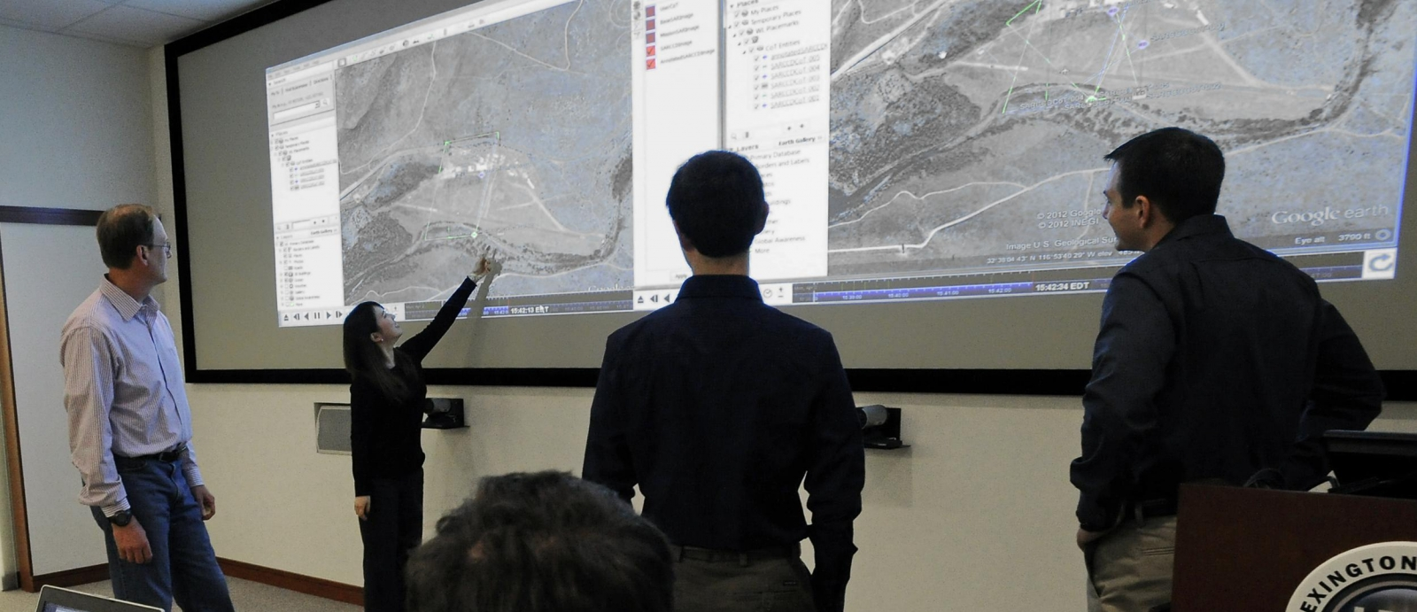 Technical staff members in the Intelligence and Decision Technologies Group review imagery of a location of interest in the maps projected in the PED Lab.