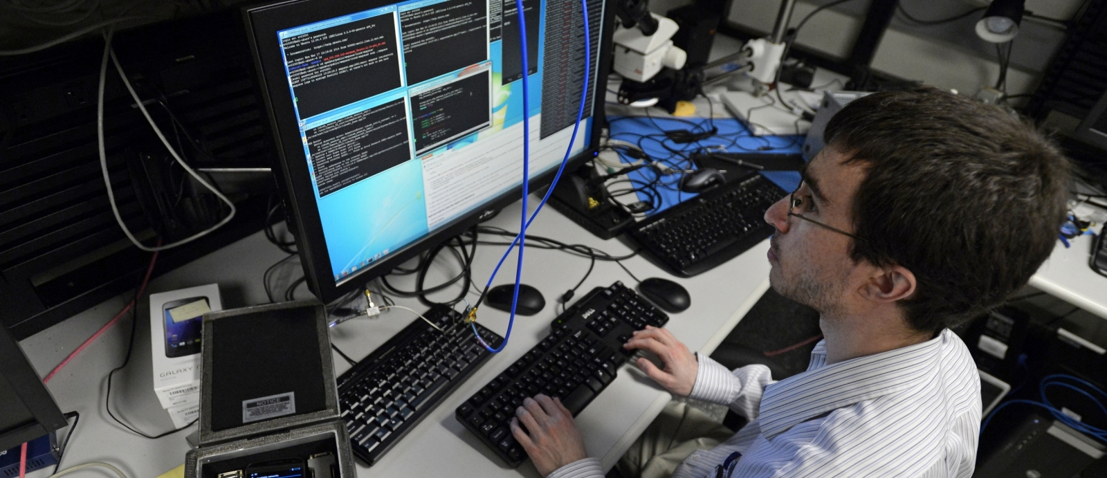 In the mobile device laboratory, a researcher in the Cyber Systems and Operations Group investigates the cyber-electromagnetic environment for handheld devices and wireless communication.