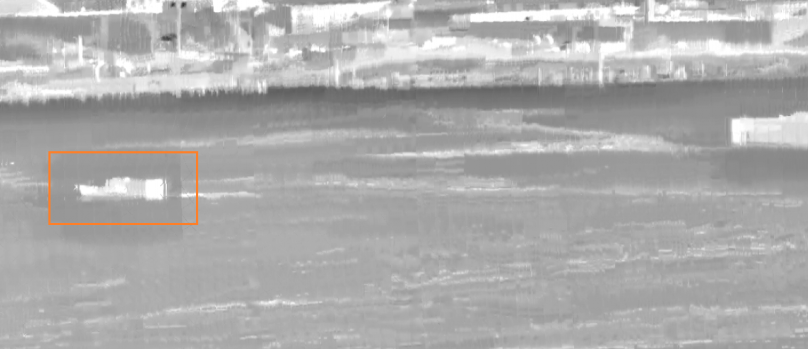 A grey-scale surveillance image of a shoreline, with a boat in the water outlined by an orange box.
