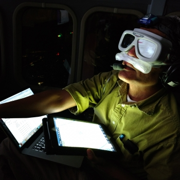 Wearing an oxygen mask inside the low-pressure cabin of the Twin Otter aircraft, Rajan Gurjar monitors the progress of the Laboratory's airborne ladar system. Photo: Brandon Call