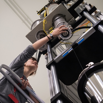 Lauren Cantley, a postdoctoral associate in the Chemical, Microsystem, and Nanoscale Technologies Group, adjusts the fiber draw tower as it pulls and spools a fiber.