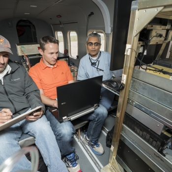 Alex Vasile works on processing initial data, while Brandon Call, from the business 3DEO which specializes in lidar technology,assists with integrating the system. Rajan Gurjar (right), is putting together plans for a local flight test. Photo: Glen Cooper
