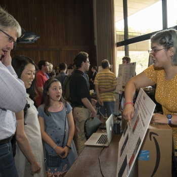 Isabel MacGinnitie, right, a student in the Build a Cubesat course, explains her project to visitors at the Stratton Student Center. Photo: Glen Cooper