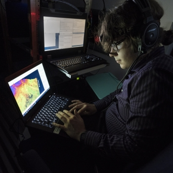 a summer research student monitors a laptop with lidar data while sitting in an airplane.