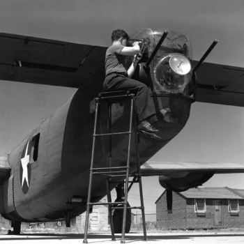 An ASG airborne fire-control radar is installed by a Rad Lab technician in the rear of a gun turret of a B-24. Photo: MIT Museum.