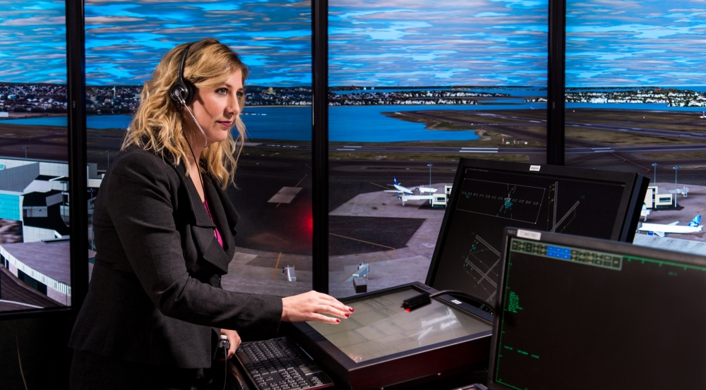 The facility's control tower simulator includes prototypes for surveillance, flight data collection, and traffic management decision support. Seen here, a Laboratory staff member controls aircraft at a simulated Boston Logan International Airport.