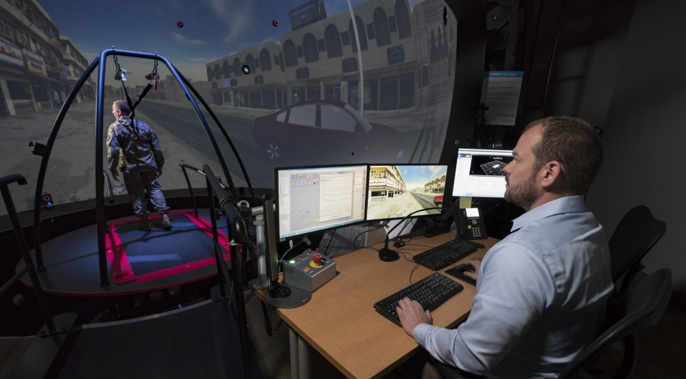 The STRIVE Center enables the assessment of cognitive and physiological performance as a person interacts with a virtual environment. The researcher above is monitoring the person's performance.