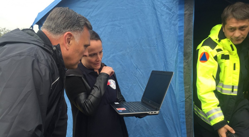Stephanie Foster briefs DHS S&T Under Secretary (Acting) William Bryan on the Next-Generation Incident Command System (NICS) as he observes its use in water-rescue operations. Photo courtesy of DHS S&T