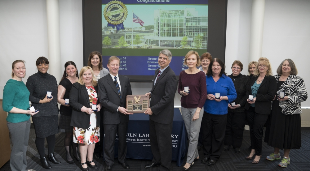 Holding the 12th consecutive Superior Security rating plaque are Shawn Daley, head of Security Services, left, and Eric Evans, Laboratory director. Joining them are representatives from the groups and divisions audited for the 2017 security review.