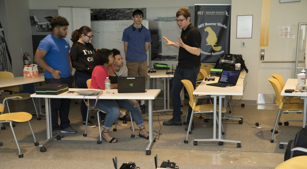 Students sitting around tables discuss the upcoming race surrounded by laptops. Two RC cars are stationed on the floor.