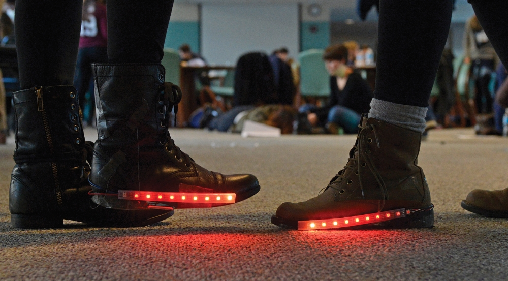 This course provides instructions for programming a wearable circuit board that measures resistance from a pressure-sensitive conductive sheet in the heel of the shoe. When resistance changes, red lights are triggered.
