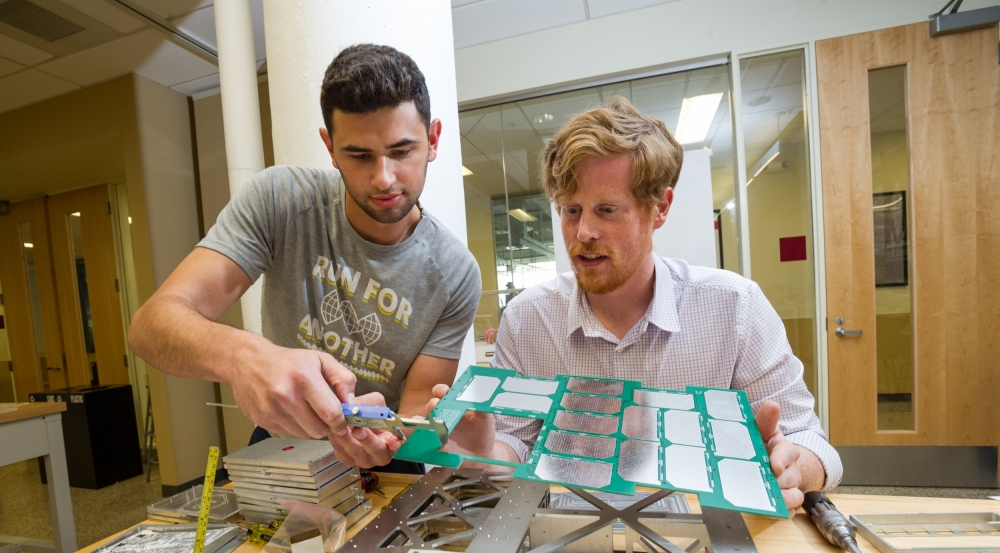 The Lincoln Scholars Program allows full-time graduate study at a local university. Above, the scholars attach panels to Boston University's first CubeSat and continue their Laboratory work in satellite aerodynamics.