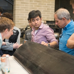 JHO team examines one of the aircraft's carbon fiber wings, constructed by the student team in AeroAstro's Building 33 Neumann Hangar. Photo: MIT News